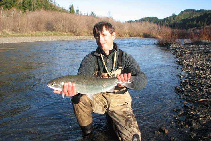 Guide Andrew Harris with a steelhead just a few miles upstream from the ocean.