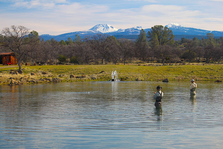 Two anglers fish the lower pond with Mt Lassen in the background.